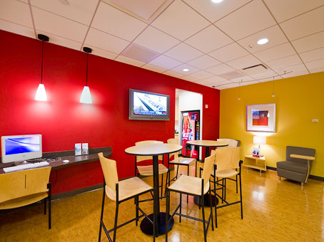 red & yellow wall with small round high table and a chairs