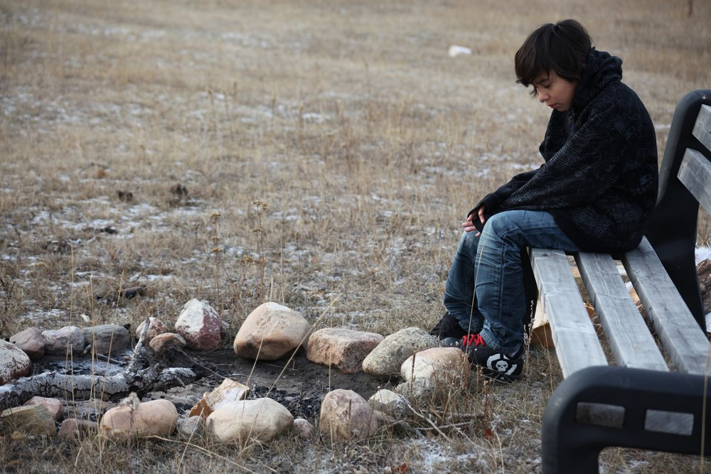 cree_male_youth_by_firepit.jpg