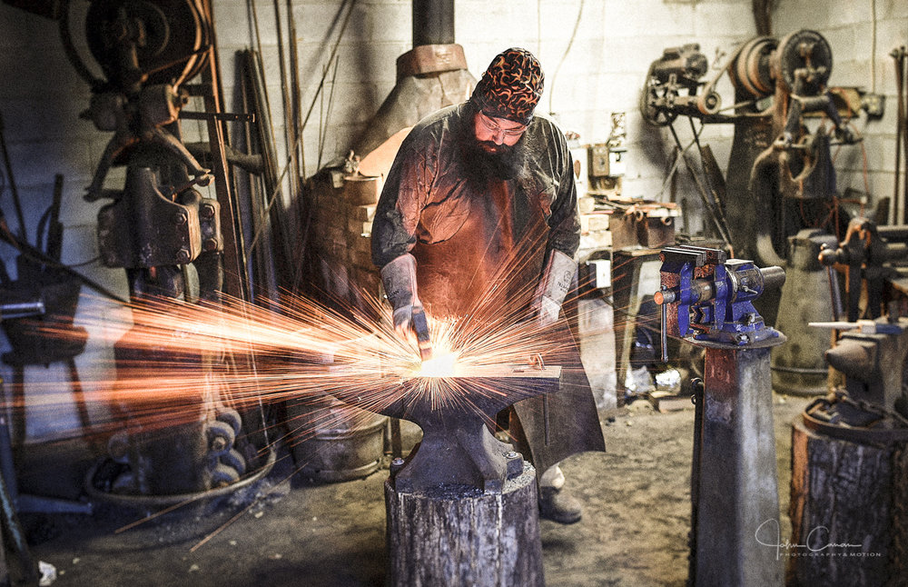 """Forging a samurai sword blade prior to his appearance on History Channel's """"Forged in Fire"""" reality TV series. Bladesmith Erin Aylor Enfolds Life Lessons Into Steel."""