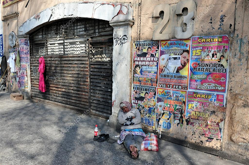 A homeless woman sleeps on the streets of Mexico City in front of posters reflecting Americanization.