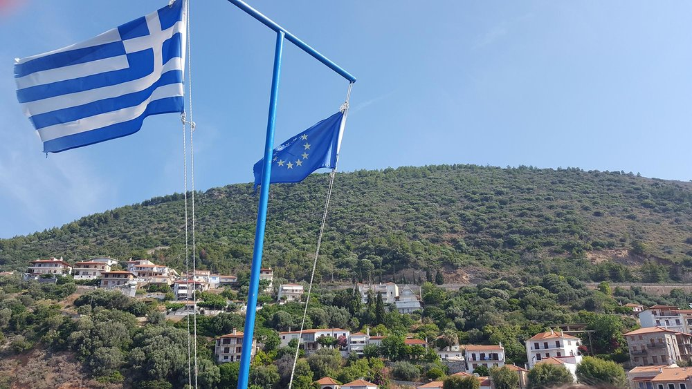 Monistiraki view up hill with flags.jpg