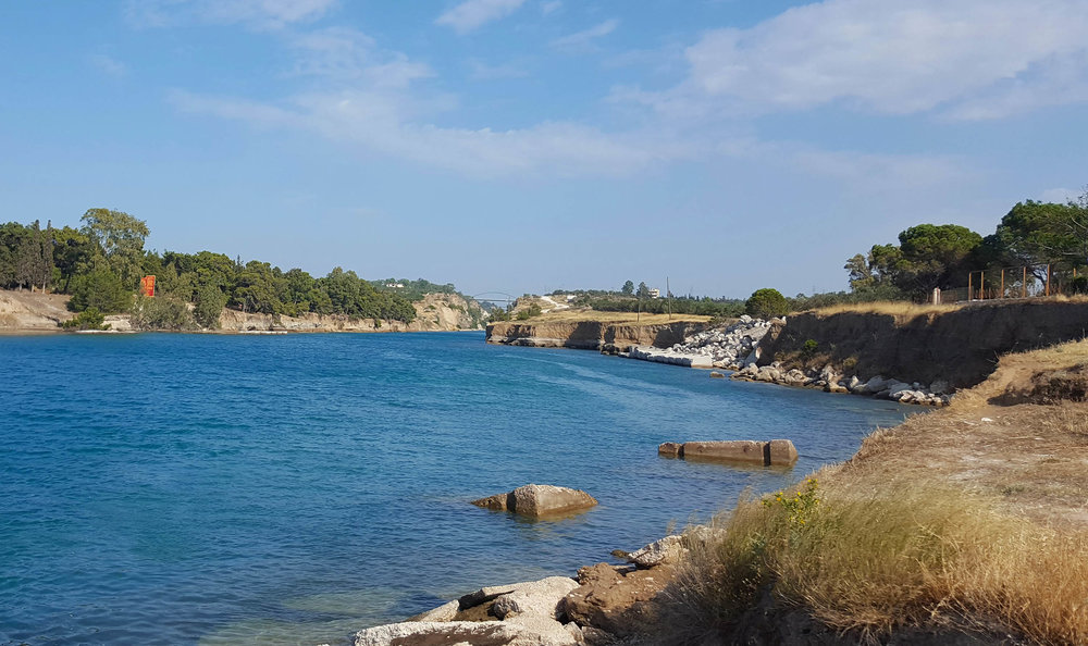Corinth canal bridge and diolkos enters water.jpg