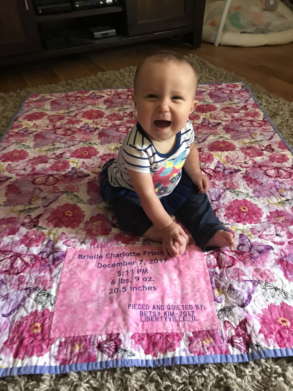 Here is sweet Brielle smiling at her mom and dad on her butterfly quilt!  Thanks for sharing this precious photo!