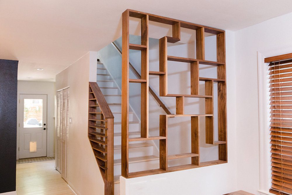 This functional stair-end offers shelving and design (walnut).