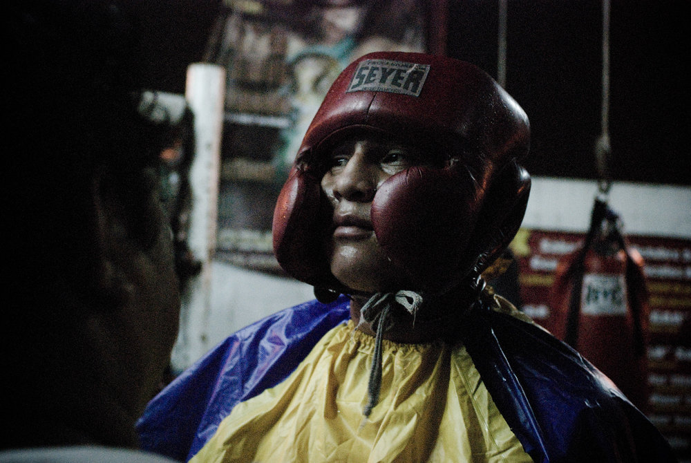 Boxer glances at his sparring partner before entering the ring at Lopez's boxing gym.