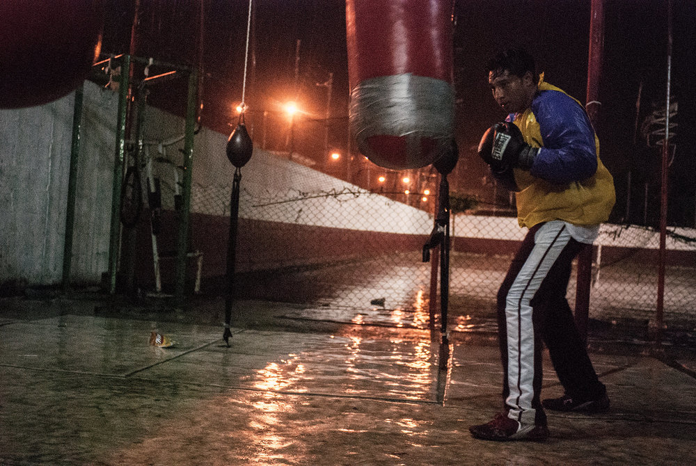 In the outdoor boxing gym of coach Lopez, a boxer works the punching bag on a rainy night.