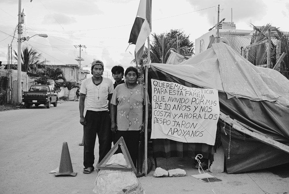 A family protesting eviction from their home. The touristic outburst in Playa Del Carmen caused the expansion of the city. Many families were evicted from their homes in order to build new luxurious condominiums to accommodate tourists.