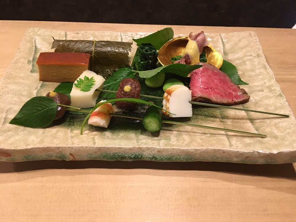 Hassun  dish ( 八寸): it is named after the size of the dish. It has both foods from the sea and the land, therefore, my dish has sea food as well as beef!    The ash on the plate is over flowing, just like the narrow passageway in a mountain after a spring rain.