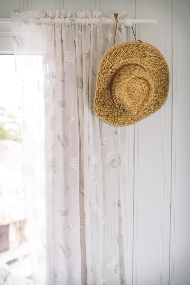 sommerhatt henger på gardinstang i hyttestua-1.jpg