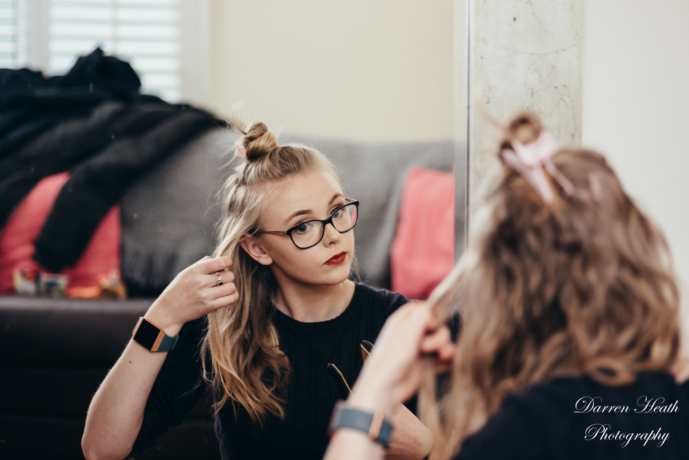 Bridesmaid in mirror styling her own hair