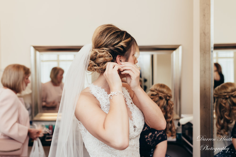 Bride in dress and veil putting in her earrings