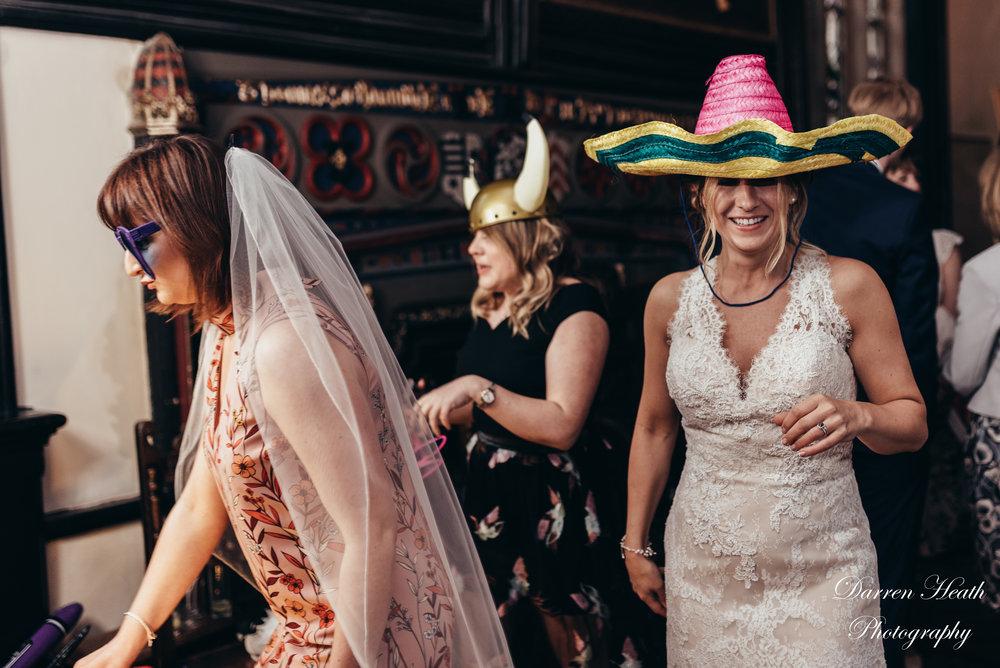 Bride wearing oversized hat at magic mirror