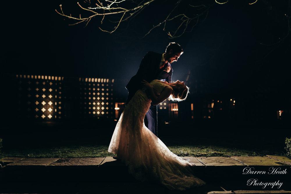 Nighttime backlit bride and groom portrait outside Samlesbury Hall