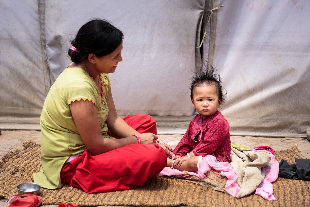 Laxmi and Shambridi outside the tent they've lived in since the 2015 earthquake damaged their home.