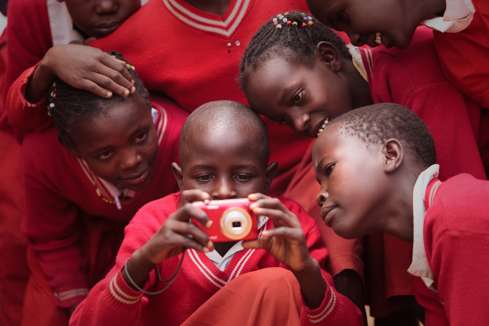 Children at Intimigom School in Kenya learn to use a digital camera, supported by The Kilgoris Project.