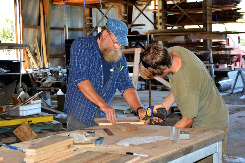 James and Steeve Moore building seed threshers in the Golden Rule woodshop.