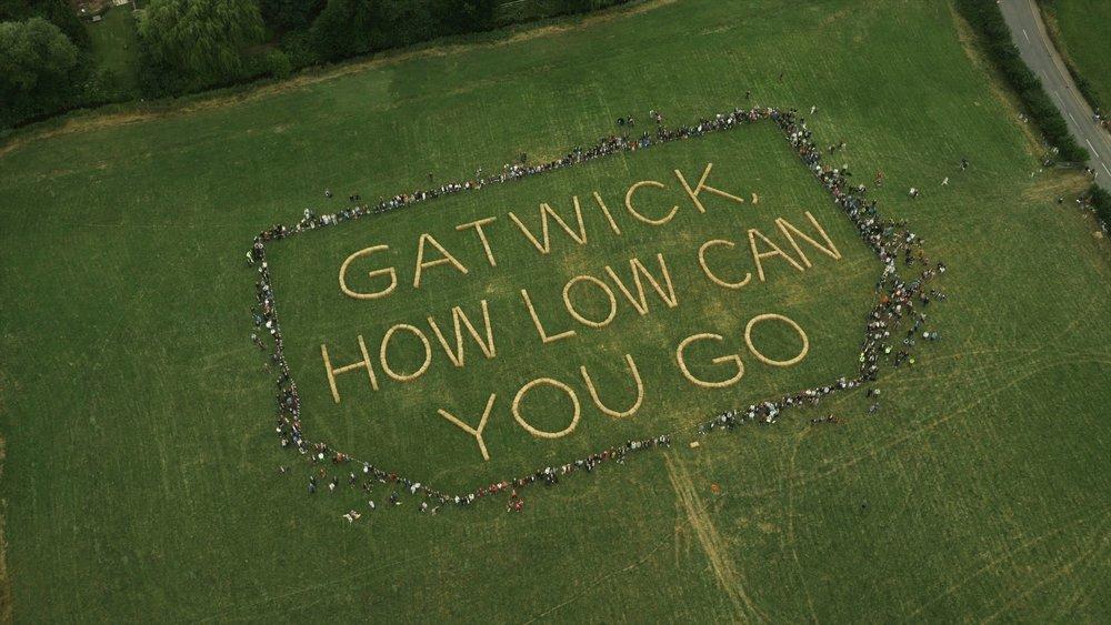 Villagers surround message written in bales of straw