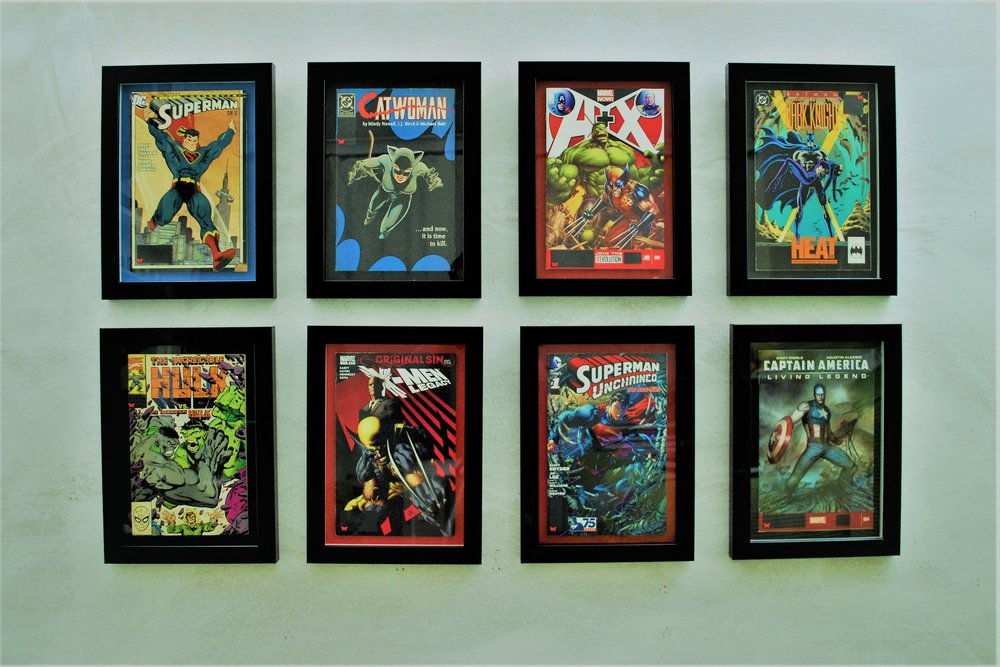 comic book classics, highlighted by colour mounts, float mounted and framed within a glossy black.