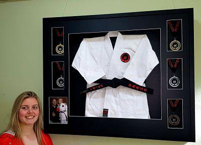 Framed karate gi with black belt and competition medals