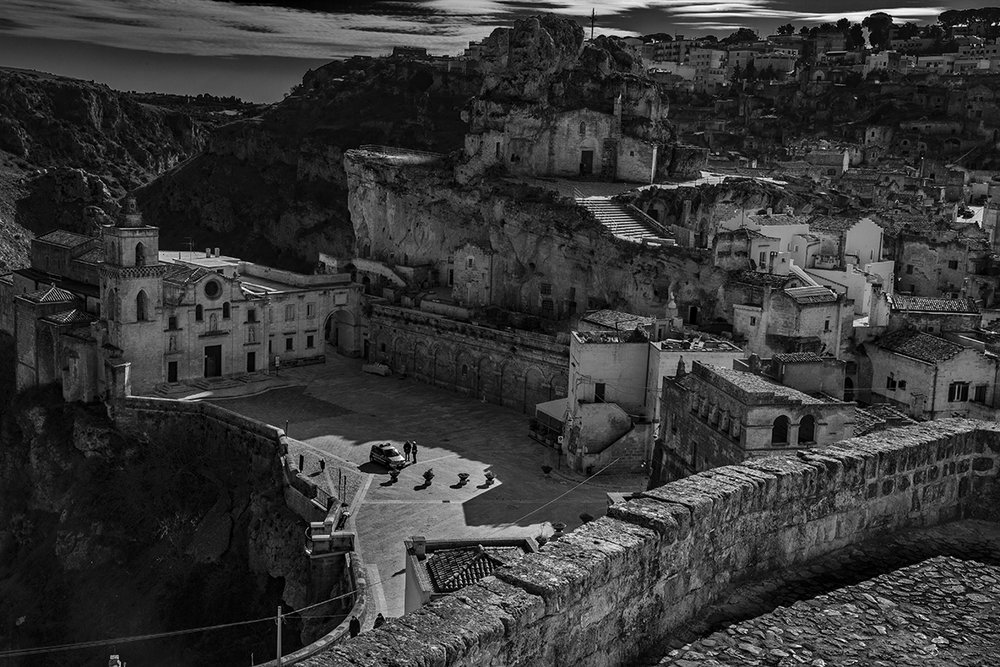 Matera, in Basillicata, southern Italy, settled by bands of people more than 50,000 years ago and as a town by the Romans in the 3rd century BC. It's effortless beauty asks many questions about how it is that in the times of bands and tribes we humans, using local materials and minimum effort in our designs, were able to create something which 2400 years later, still seems to be more complete and satisfying than most of what we build today.  Jan. 17; photo Robert Golden    The necessity was created by the needs of survival, to defend oneself from other human beings and wild animals, and later to protect ones domesticated animals from the wilder ones.    I edited them – a thing I always refer to as 'printing' although it is not strictly printing since I am darkening, lightening, and changing the image to favour the contrast I prefer, and so on, in Photoshop as a digital file. The actual printing on paper may come later.    Because people still inherently trust the apparent truthfulness of the photographic image but also because they inherently know that Photoshop can weave dreams, I am often asked how much manipulation have I done? I have to admit that the question always irks me, as no one ever asked me that previous to Photoshop. Then, with an enlarger, photosensitive paper and chemicals, I darkened, lightened and changed the contrast as well but was never asked the question.