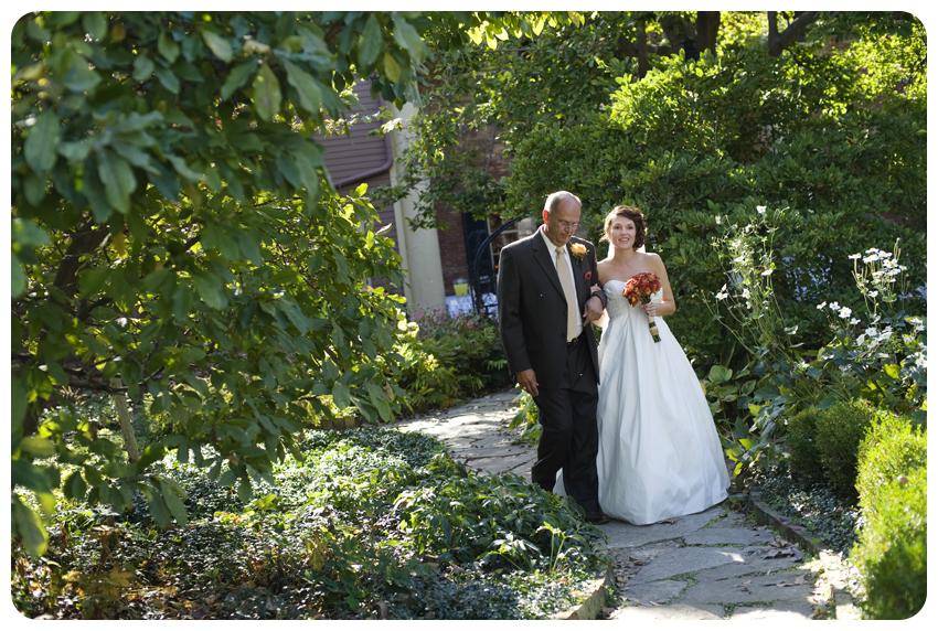 kentucky garden wedding bride walks down aisle with father orange roses