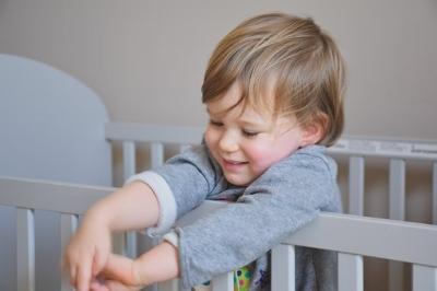 toddler boy standing crib.jpg