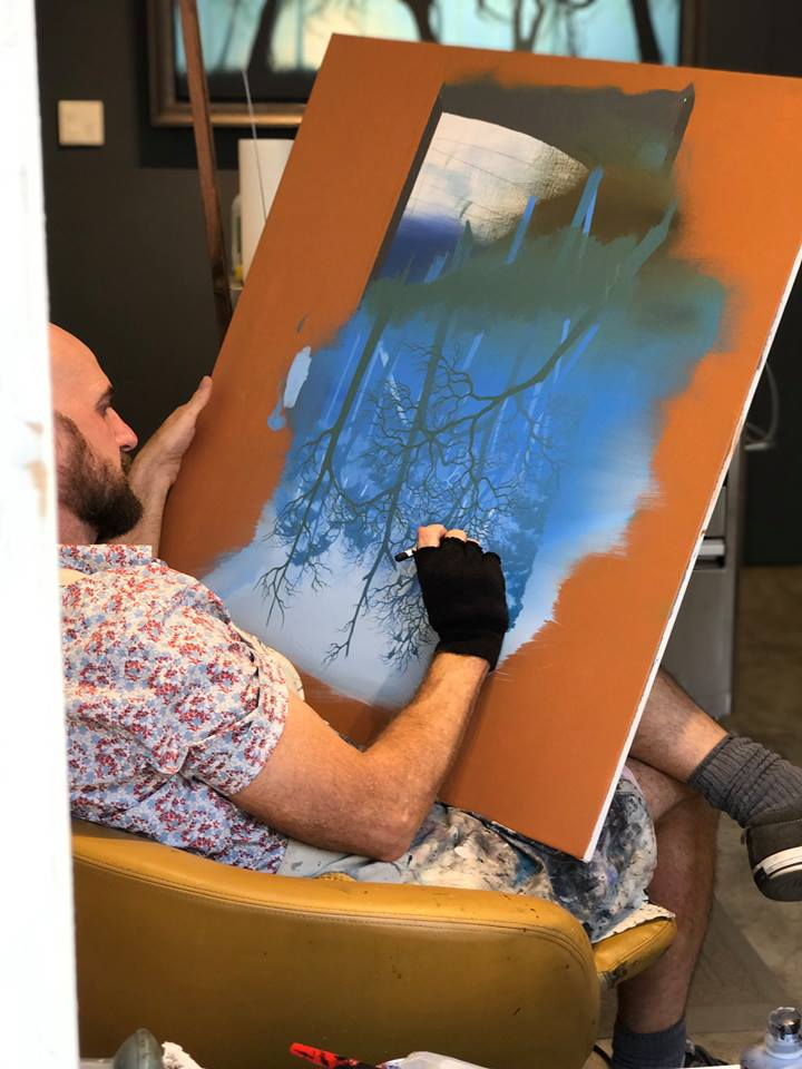 Tanner, embellishing a giclée for a customer
