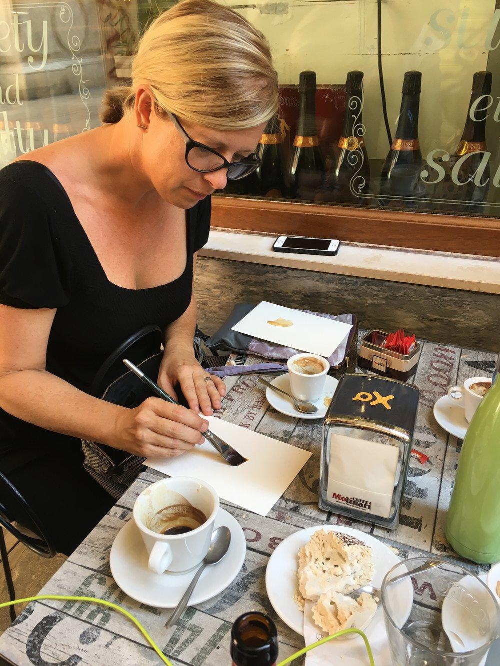 Danielle Krysa painting with coffee in a Venetian café