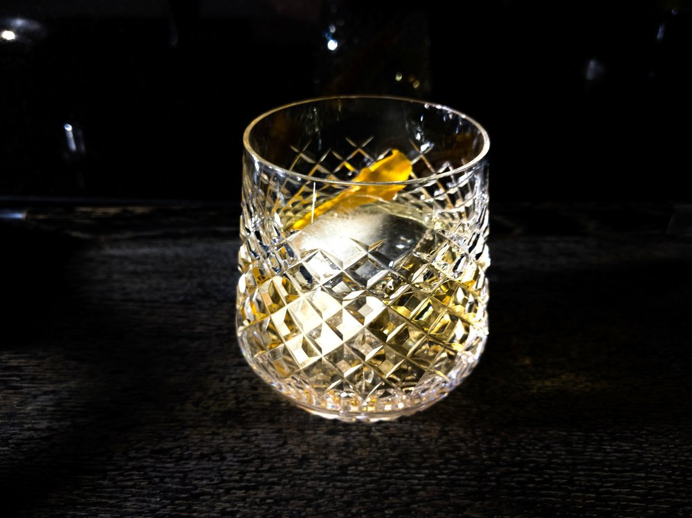 CARAWAY ON THE ROCKS - Generous pour of Dr. Zzyzx Caraway vodka over rocks, garnished with expressed tangerine peel