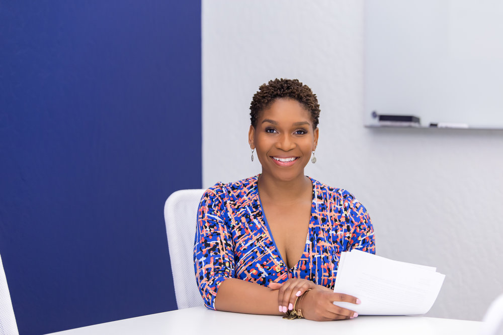Branding photography image of female, African American, business owner, holding papers and sitting at a desk, wearing colorful dress in office setting.