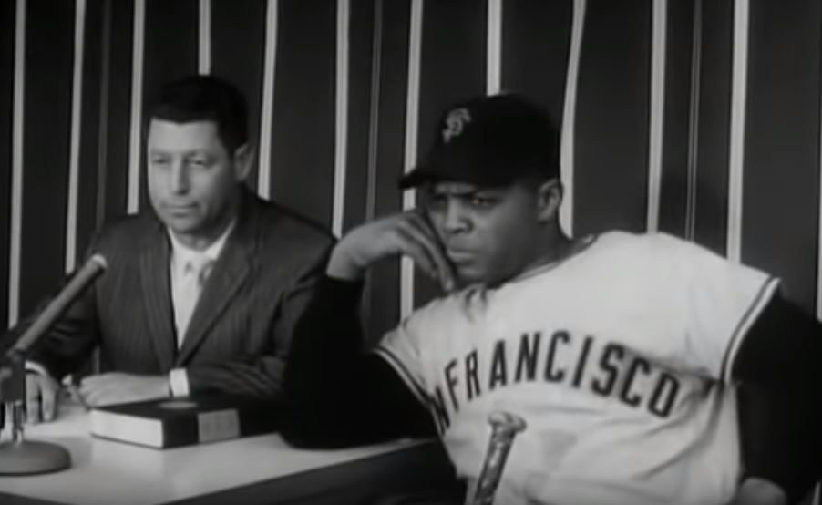 "Willie Mays deep in thought while waiting in the broadcast booth with host Mark Scott as they watch Mickey Mantle take his cuts in ""Home Run Derby."""
