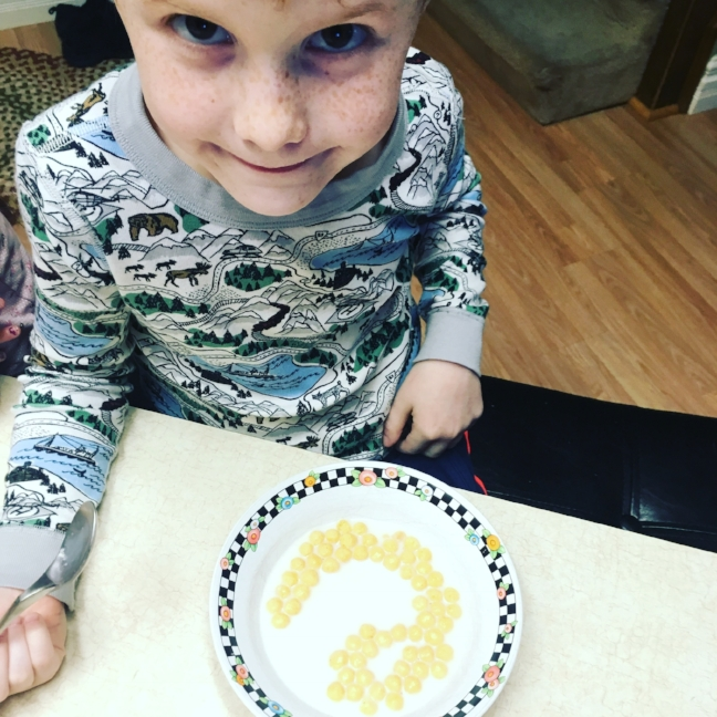 Making letters in his cereal.