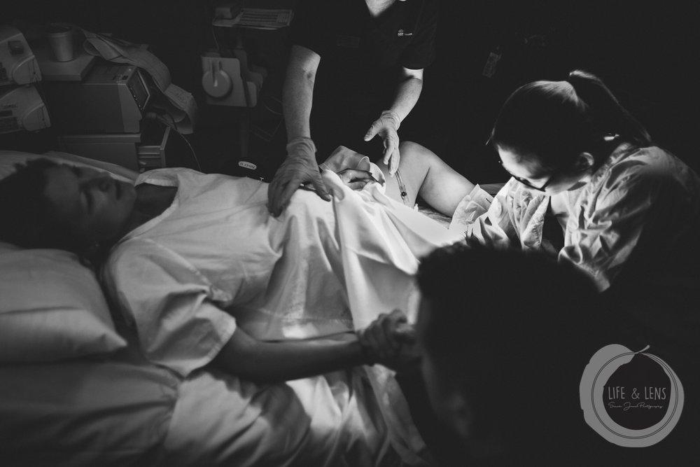 sydney birth photographer - woman having an internal exam during childbirth