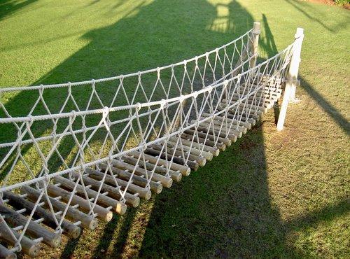 log rope bridge leading to a treehouse — rope bridges