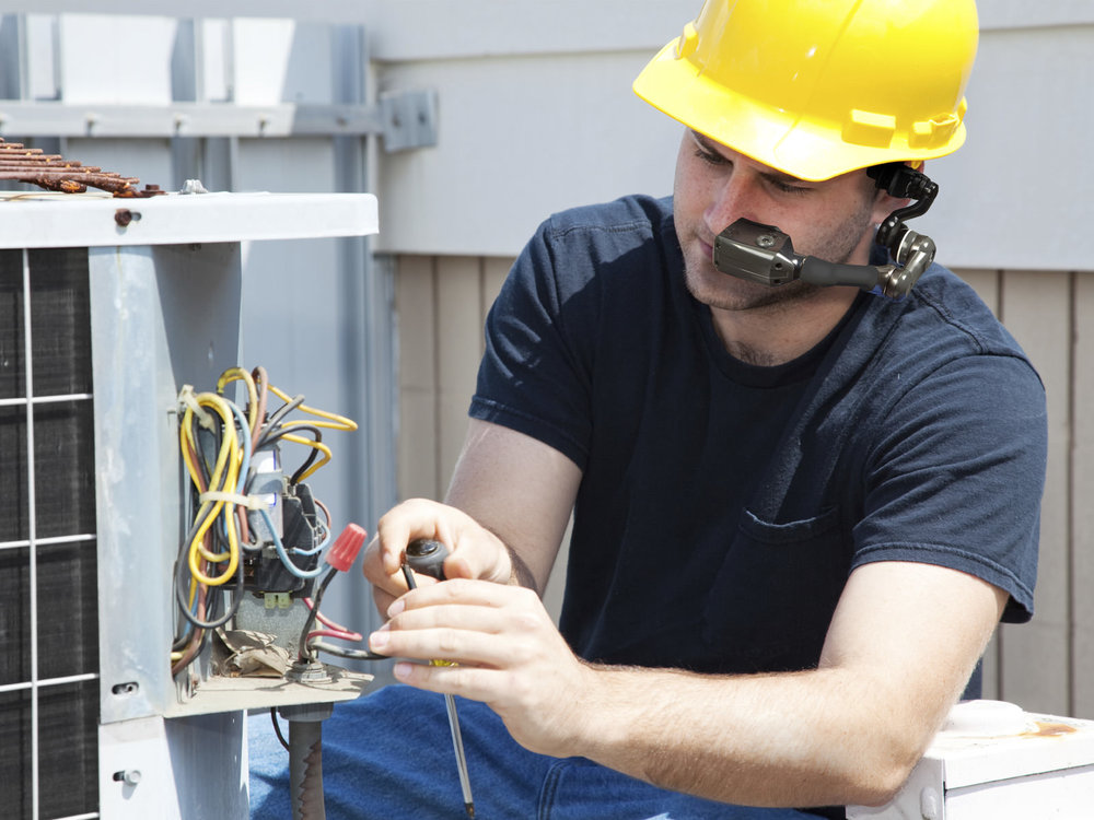 A hard hat wearing electrical engineer wearing HC1 while examining a bundle of wiring