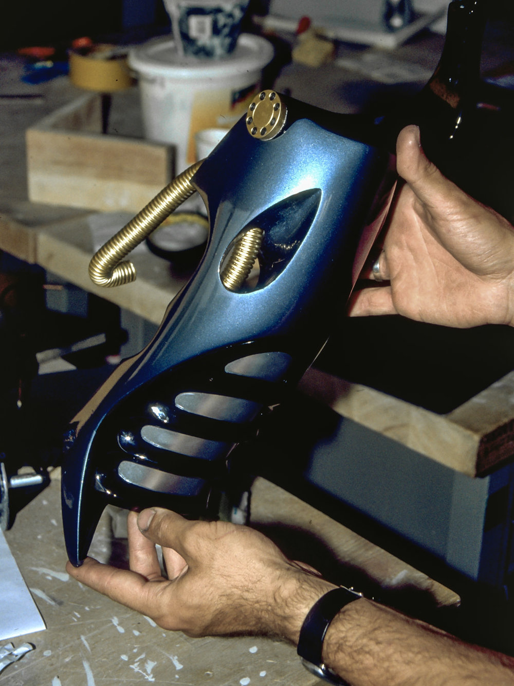 A finished part of the motorcycle in glossy blue metallic paint and gold detailing