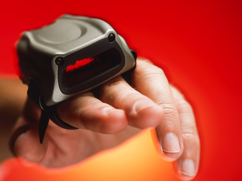 The CRS1 ring scanner worn close-up, and being worn on the left two first fingers with a red and orange background