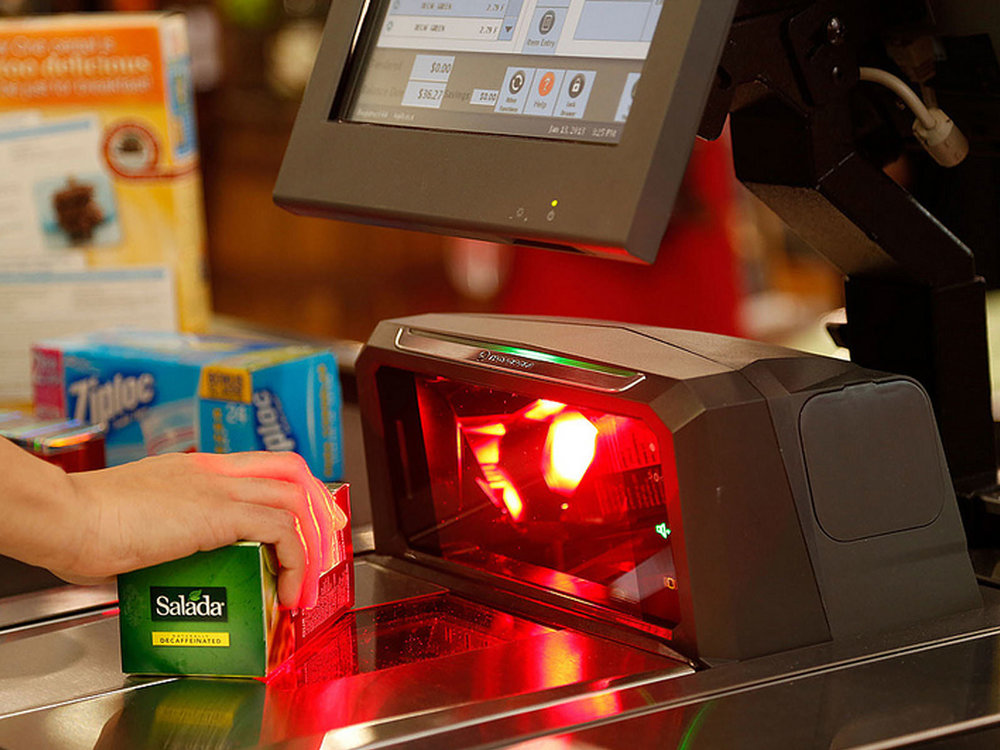 The MP6000 being used in a supermarket setting, with an object being passed in front of the main scan window and lighting up red