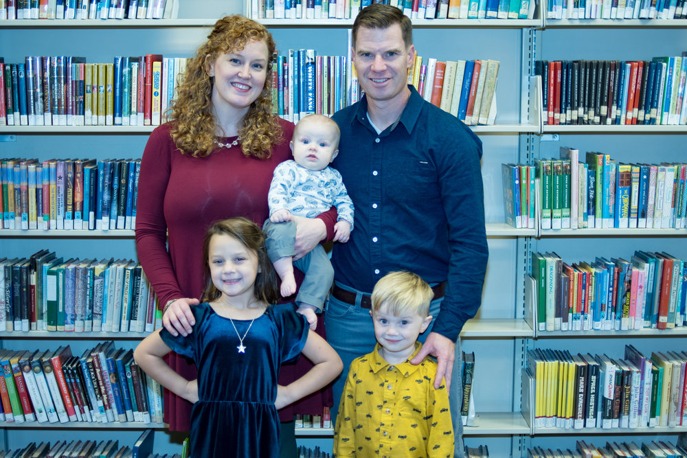 - Family portrait of a bright family who loves literature, standing in front of children books in Downtown Wilmington NC Library!