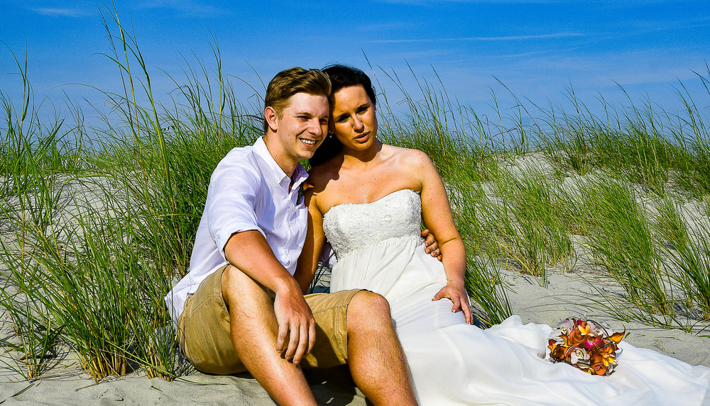 - Bride and Groom touching foreheads sitting on dunes with bouquet resting on dress.