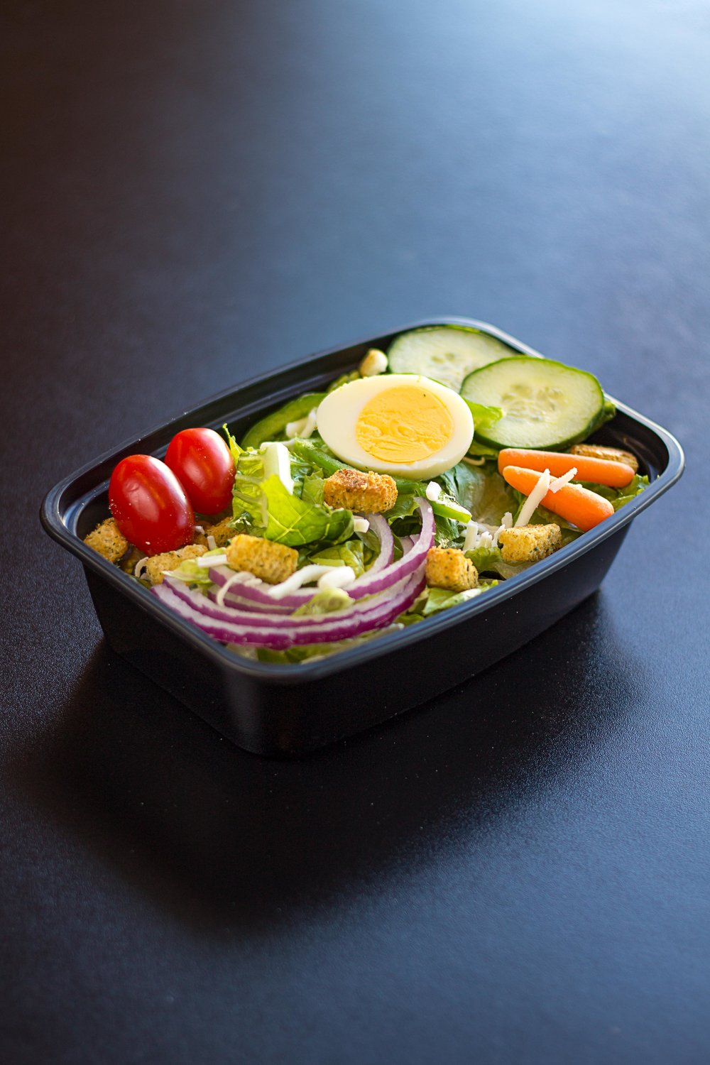 Half Garden Salad- A bed of fresh crisp romaine lettuce topped with tomatoes, cucumbers, carrots, an egg, bell peppers, red onions, cheese & croutons. Served with your choice of dressing!