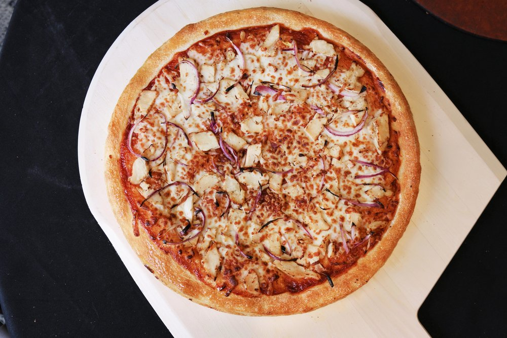 Deep Dish BBQ Chicken Pizza- Thick, freshly made pizza dough topped with barbecue sauce, chicken, & red onions.