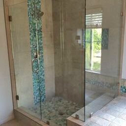 Frameless clear glass shower enclosure with door, notched panel and return, brushed nickel hardware, and clamp install.