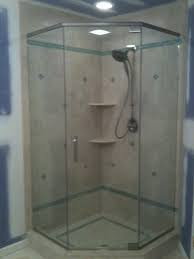 Neo-angle shower unit with brushed nickel hardware, header for support, and glass to glass hinges for the door.