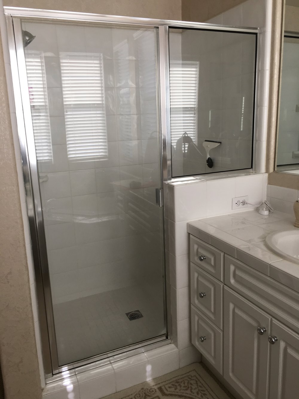 Clear glass shower enclosure with door and a notched panel with a chrome frame and hardware.