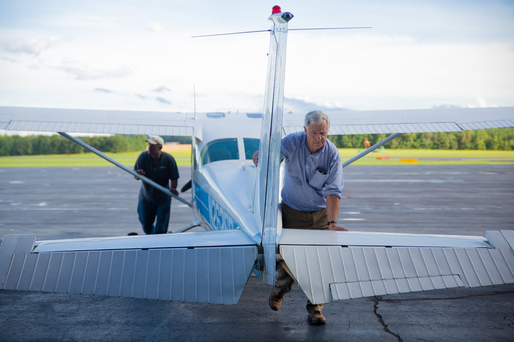"In preparation for Hurricane Florence hitting the east coast, Watkins flies one of his planes back from South Boston, V.A. Watkins and his partner in the plane's ownership, Carl Chambers, push the plane inside the hangar so that it doesn't get damaged due to sporadic hurricane storming.  ""I started flying when I was 14,"" Watkins says. ""A dentist by my family farm taught me. He didn't give me formal flying lessons; he just brought me up and said 'Here are the controls.' The airplane in those days ran for $8 an hour and $4 for the instructor. He was just a nice guy and bought planes and made them available for people to use. Today, I charge $60 for the instructor, which is me, and $130 for the plane per hour, which sounds expensive, but I try to keep costs low. I'm paying it forward."""
