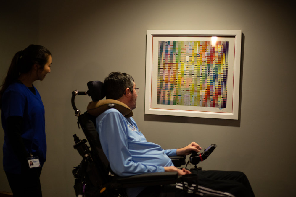 Irene Zhu, a UNC Chapel Hill senior planning on going to school to be a physician's assistant, walks with Dr. Ross through the floors of his apartment complex on the evening of Oct. 25.  On every floor of the apartment, the walls are filled with original art donated by residents of the building, forming a sort of gallery. Before being diagnosed with ALS, Dr. Ross was a photography professor at Radford University in Virginia, and still thoroughly appreciates art.