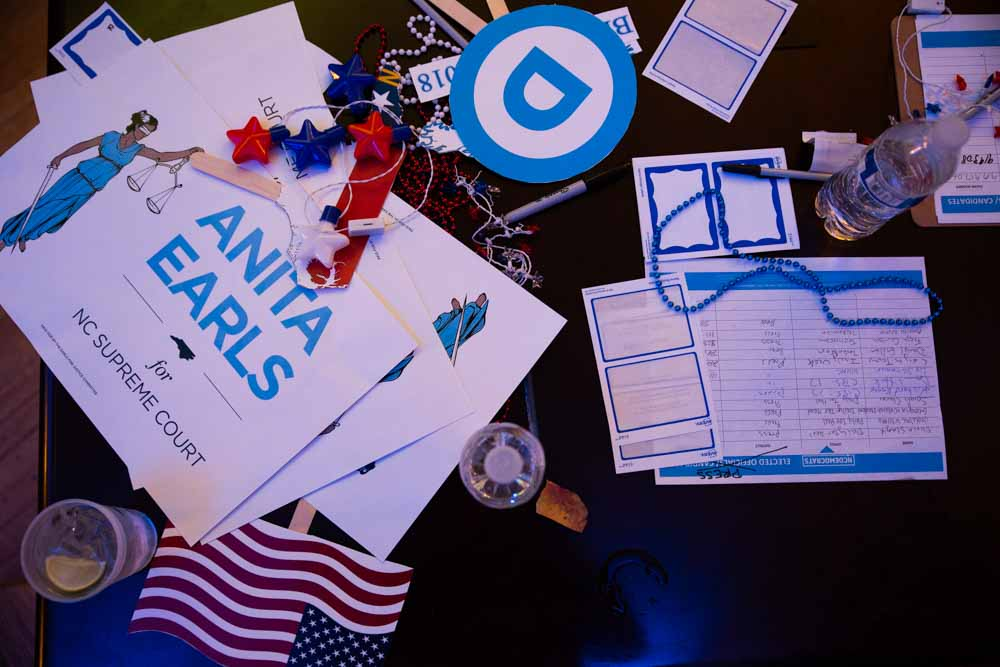 "A pile of abandoned voting day materials advocating for Anita Earls lays abandoned on a table at the North Carolina Democratic Party headquarters in Raleigh on election night Nov. 8.  ""I became an attorney because I grew up in a mixed race family,"" Earls says. ""My father was black and my mom was white. When they met and fell in love in Missouri it was illegal to get married. As I was growing up, the Supreme Court decided a case that said those covenants cannot be enforced. So I overtime saw the law as a way that could be used to break down barriers. And I saw the role that lawyers could play in that. Crossing that racial divide was essential to our survival as a family, essential to my survival. And I think equally now, coming together to bridge that divide and fix our democracy is essential to our survival."""