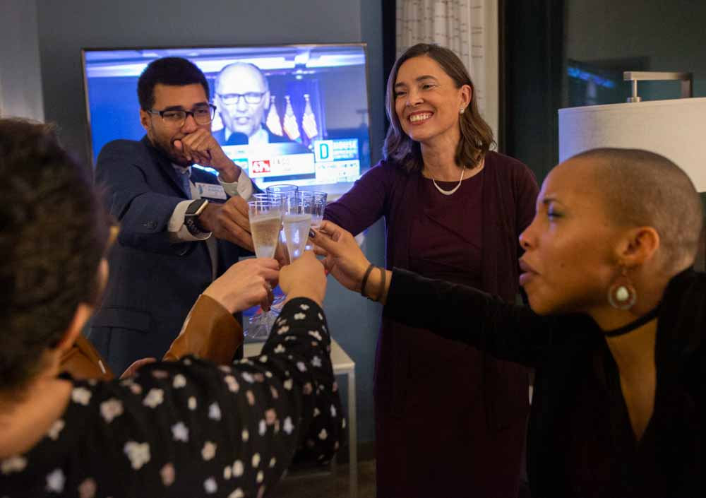 (From left to right) Back at the hotel room in Raleigh, Jackie Gonzalez, José Morales, Anita Earls and Juju Holton celebrate Earls' victory on election night.