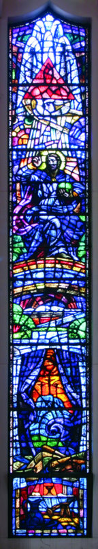 In the second window on the left we see Christ on the Cross between the two thieves (lower); above is the body in the tomb, then two rainbows dividing earth from heaven; and above that Jesus reigning in glory.